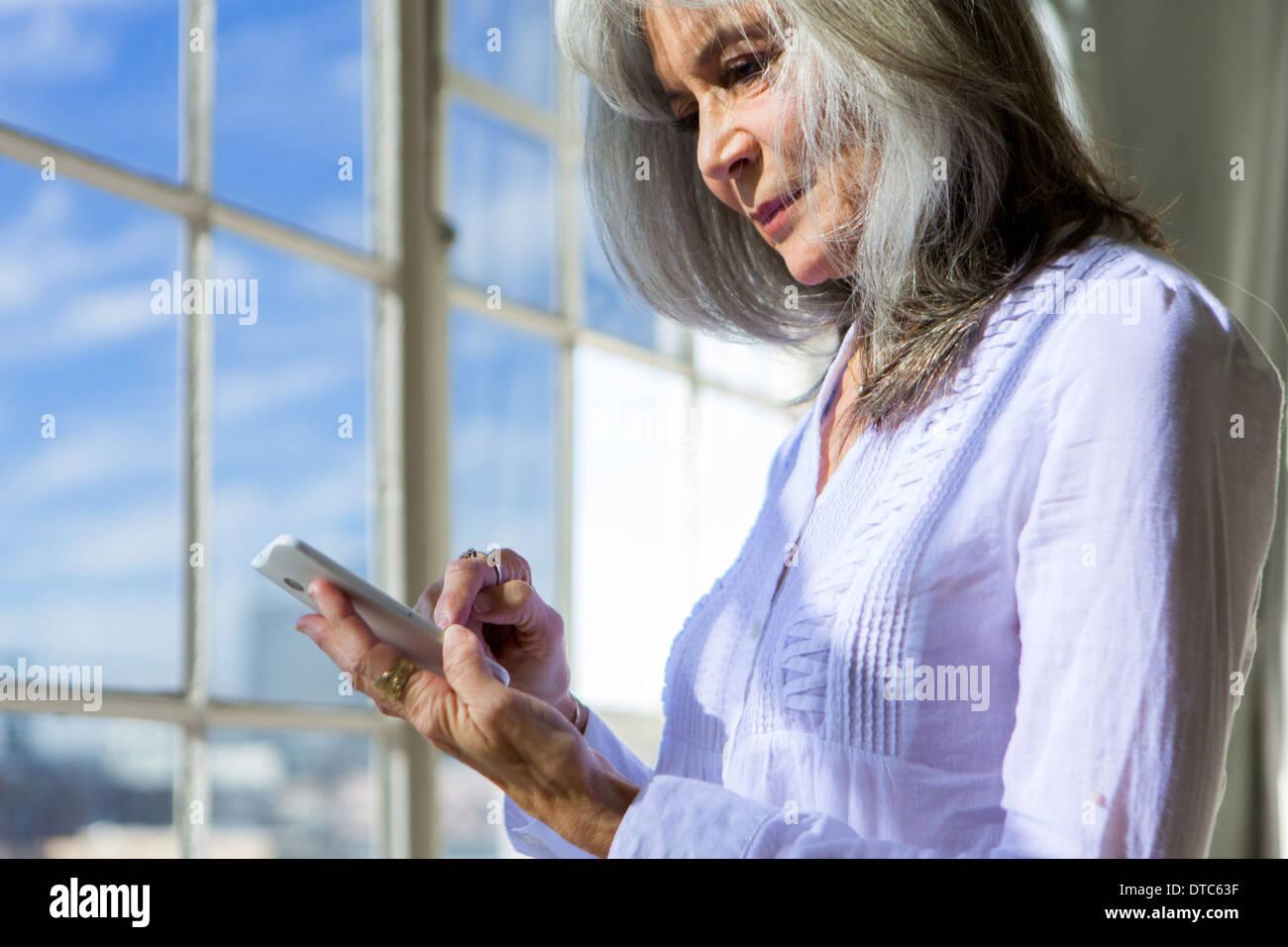 Senior woman using touchscreen on smartphone - Stock Image