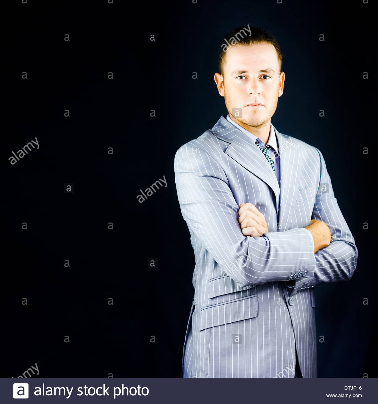 Successful wealthy influential young business man posing in a bespoke pinstripe suit with an air of authority and - Stock Image