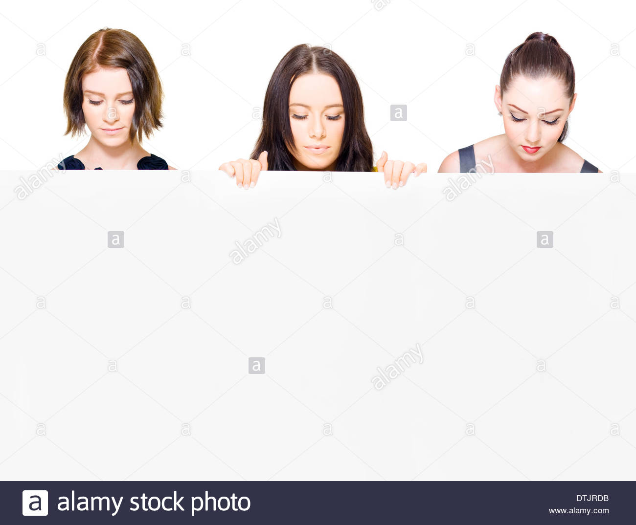 Solemn dignified women holding a blank sign and looking down with downcast eyes at the space for your important - Stock Image