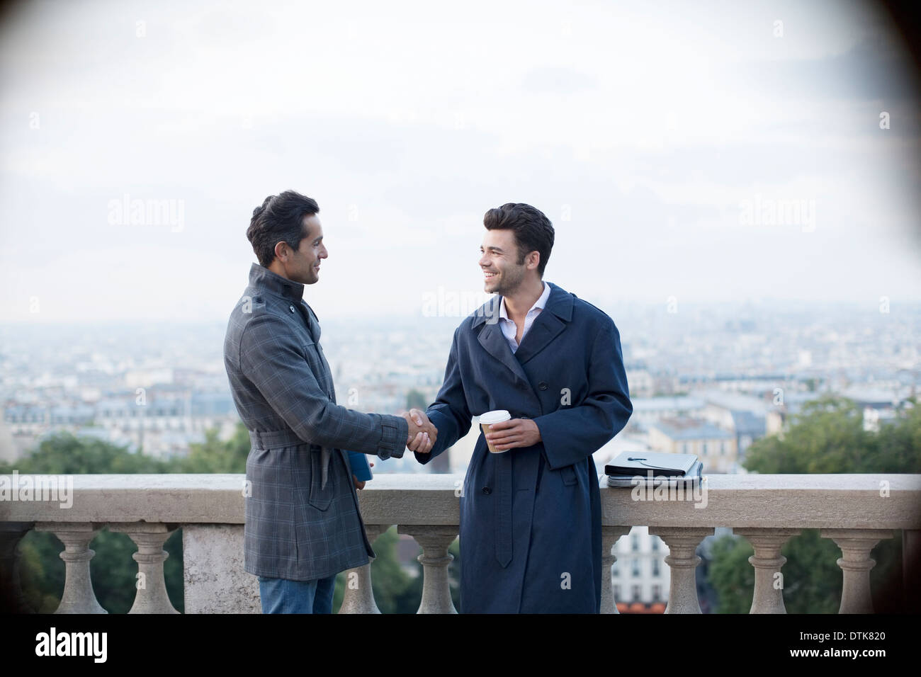 Businessmen shaking hands at railing overlooking Paris, France - Stock Image
