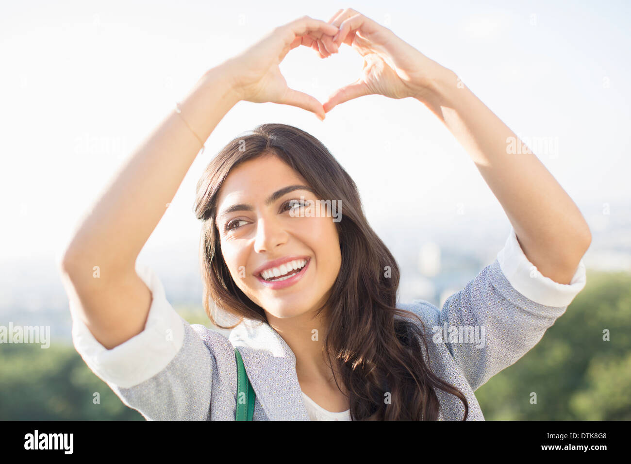 Woman making heart-shape with hands outdoors - Stock Image
