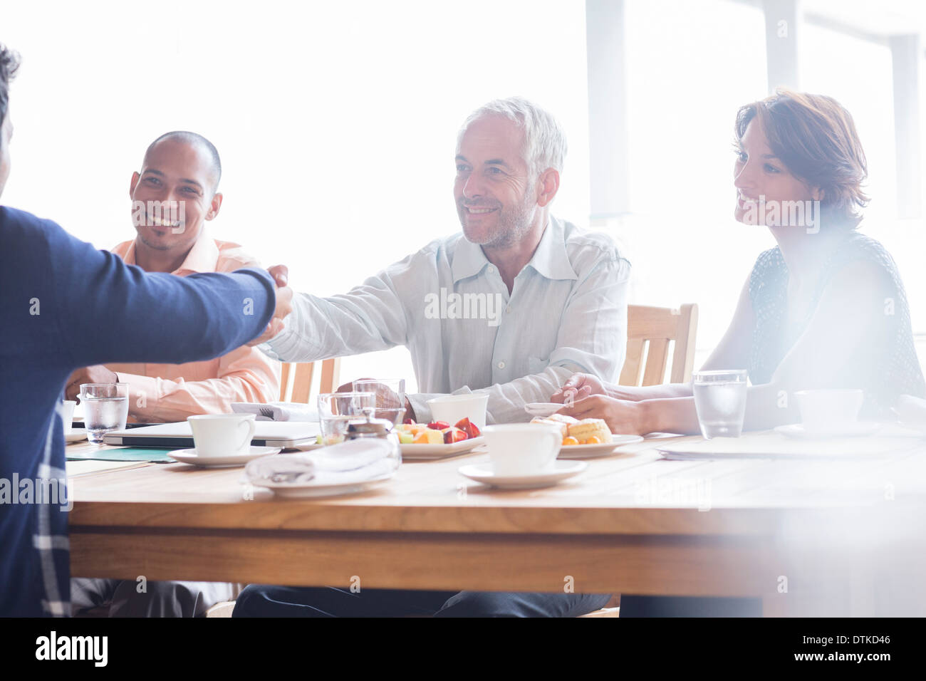 Business people shaking hands in meeting - Stock Image