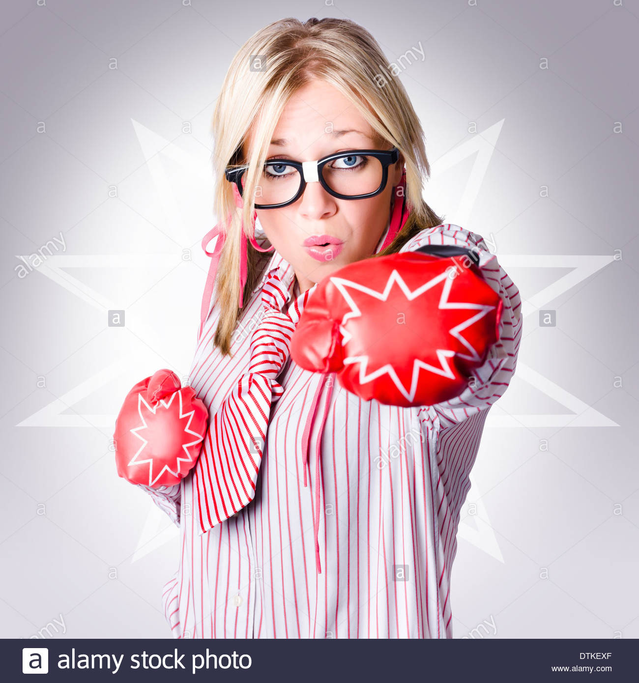 Tough business woman packing a punch of strength and power wearing boxing gloves on starburst background - Stock Image