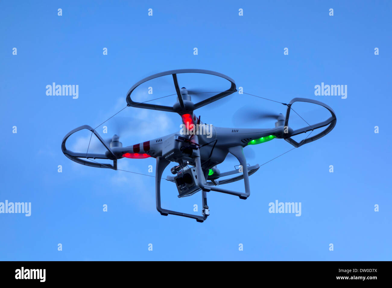 Miniature drone / unmanned aerial vehicle / UAV equipped with camera in flight against blue sky with clouds Stock Photo