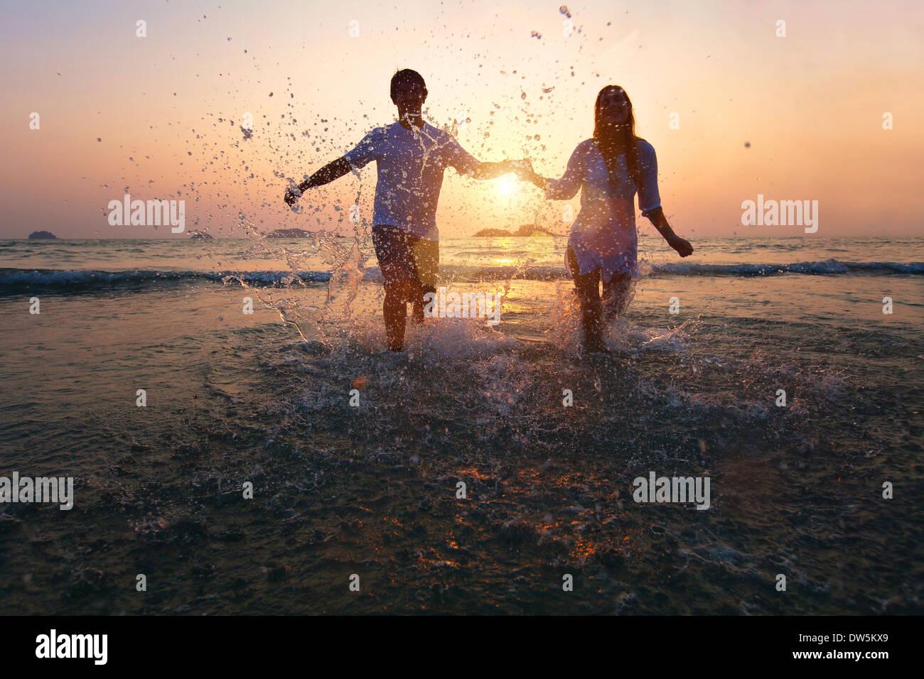 happy couple enjoy sunset on the beach - Stock Image