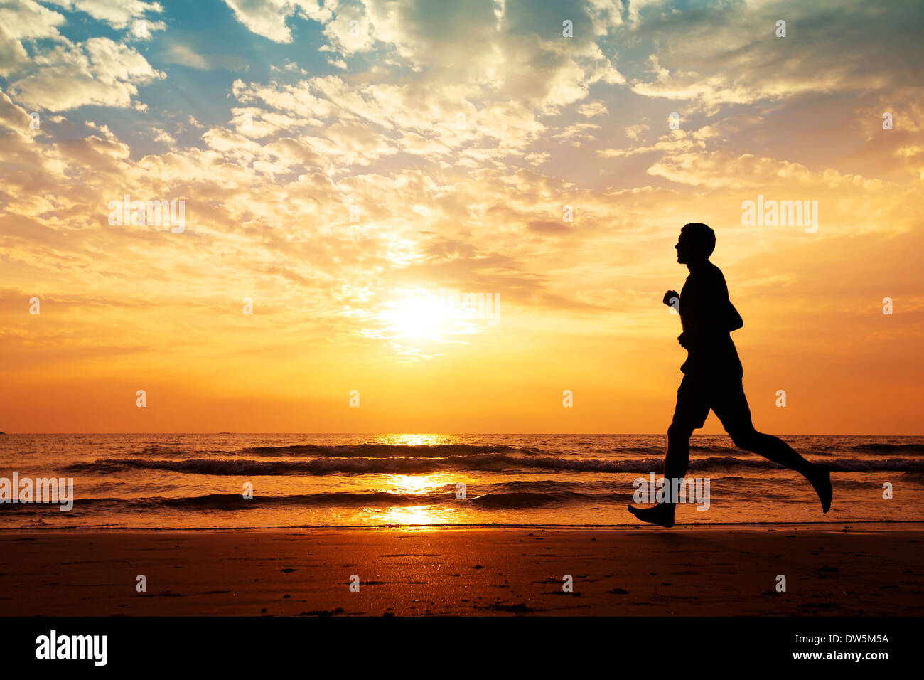 silhouette of man running on the beach at sunset - Stock Image