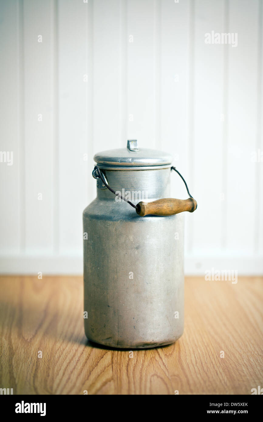 vintage milk can on wooden floor - Stock Image