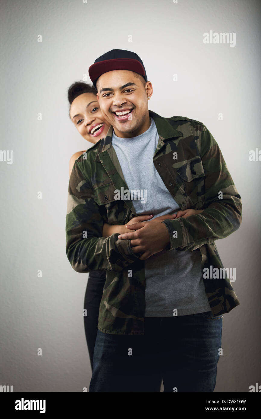 Cheerful hispanic young couple together on grey background. Young woman with her handsome boyfriend smiling at camera. - Stock Image