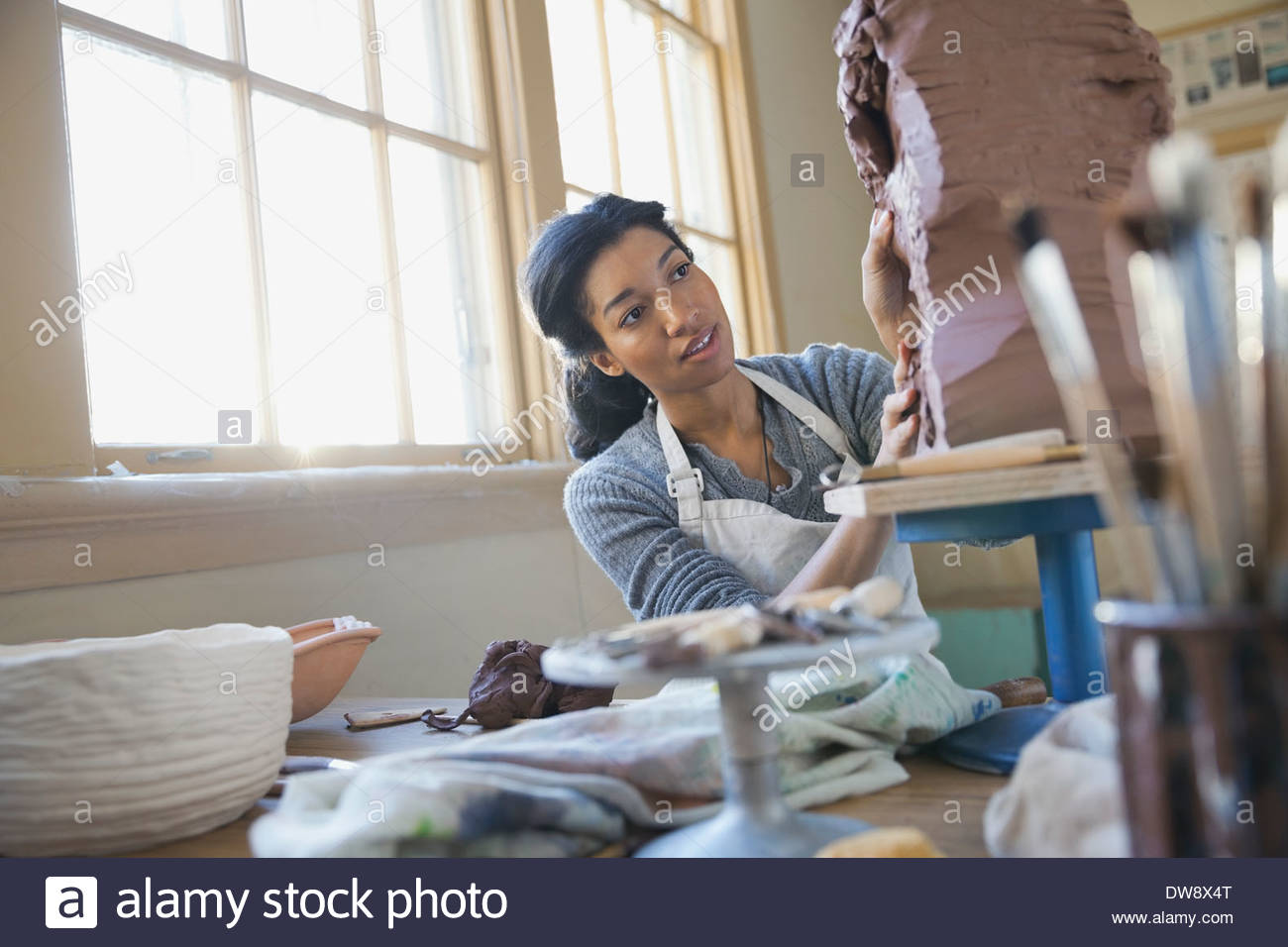 Student working on clay sculpture in art class - Stock Image
