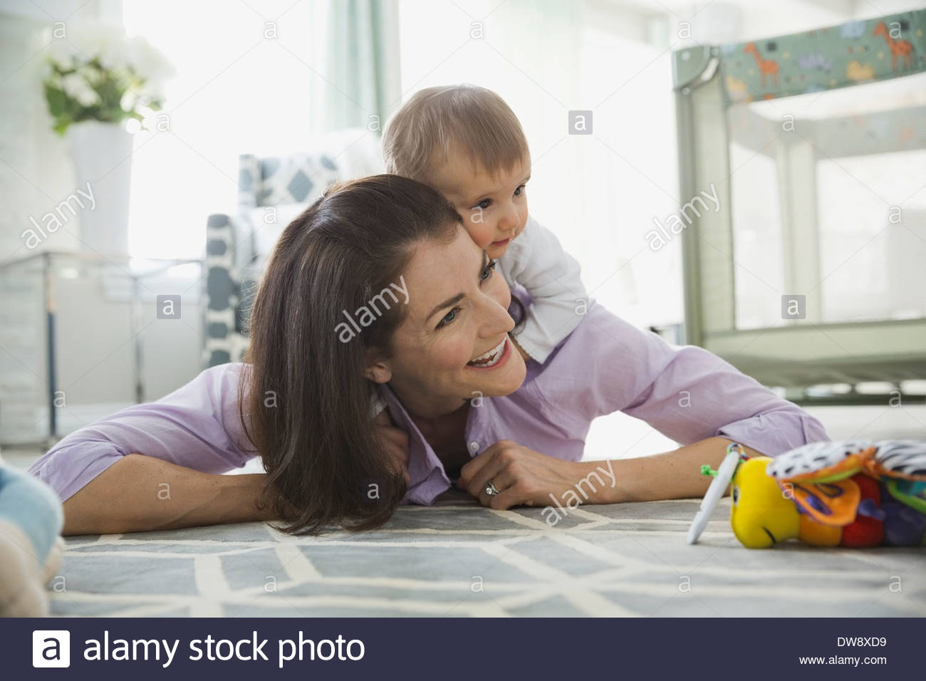 Cheerful woman playing with baby girl at home - Stock Image