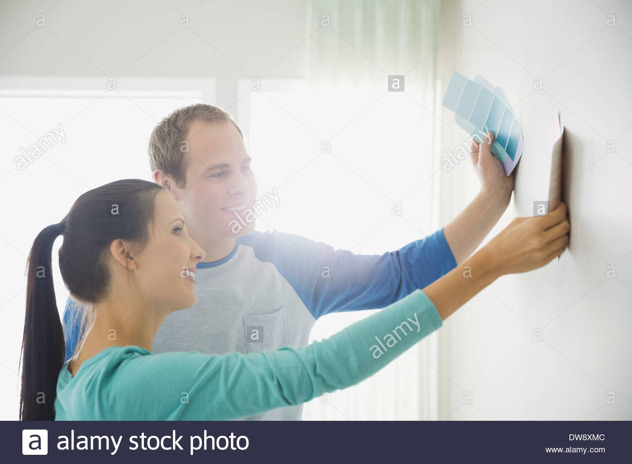 Young couple holding color swatches against bare wall - Stock Image