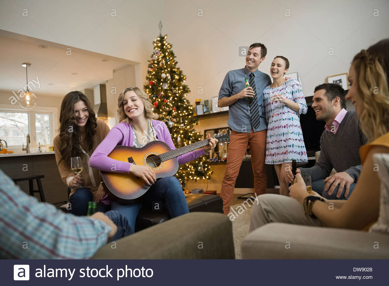 Friends spending leisure time together at home during Christmas - Stock Image