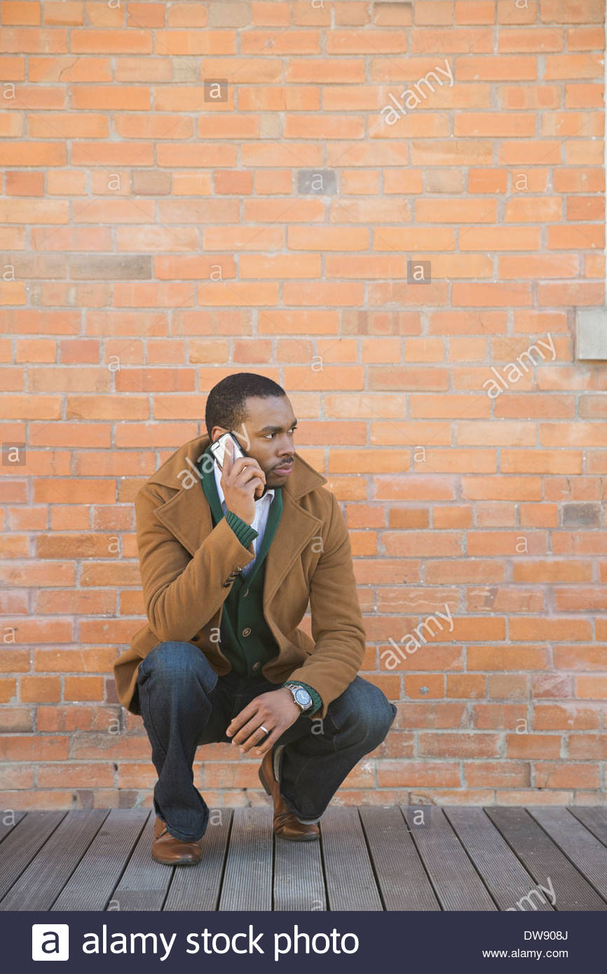 Man with smart phone crouching against brick wall - Stock Image