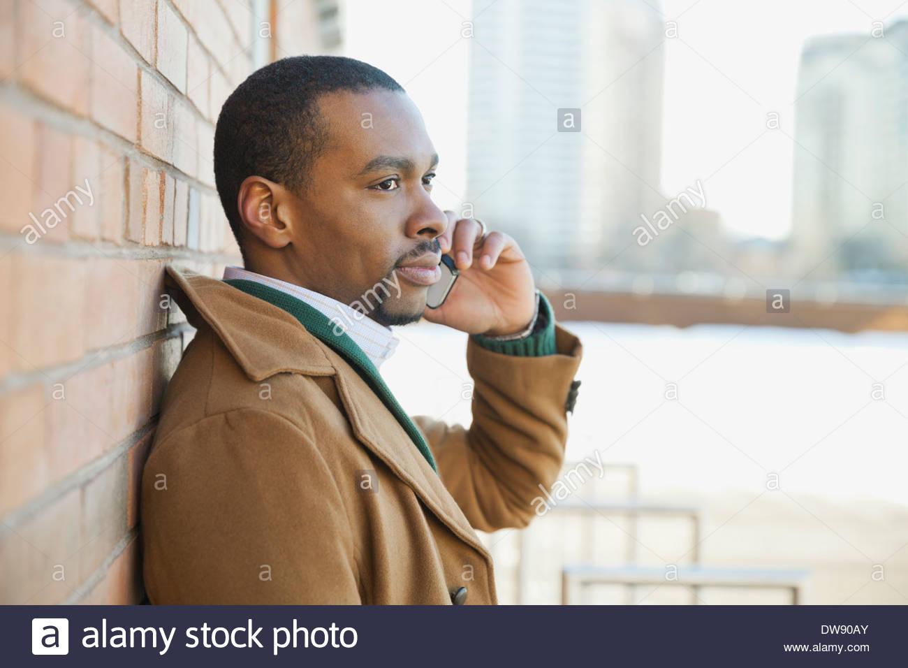Man using smart phone outdoors - Stock Image