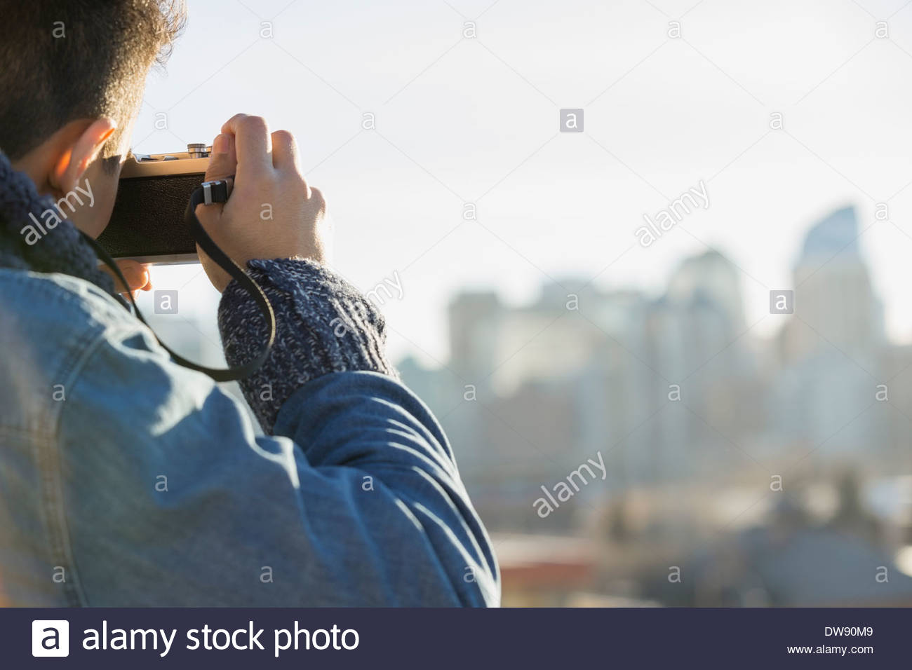 Rear view of man photographing cityscape - Stock Image