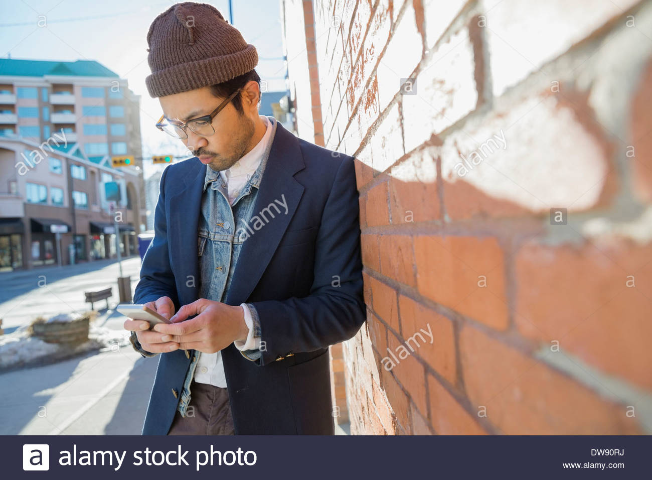 Man text messaging on smart phone against brick wall - Stock Image