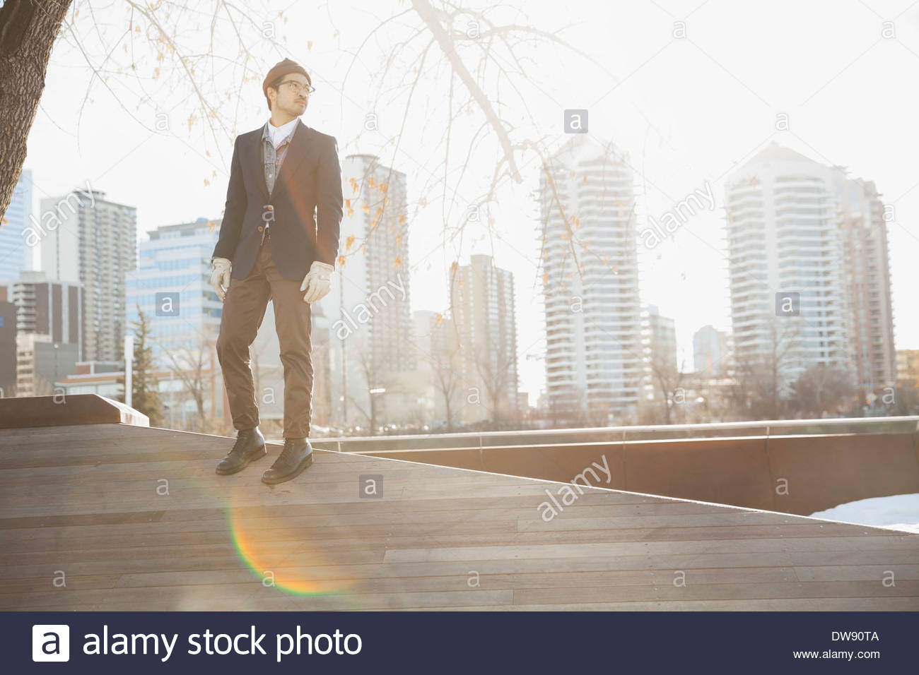 Man standing on wooden slope against cityscape - Stock Image