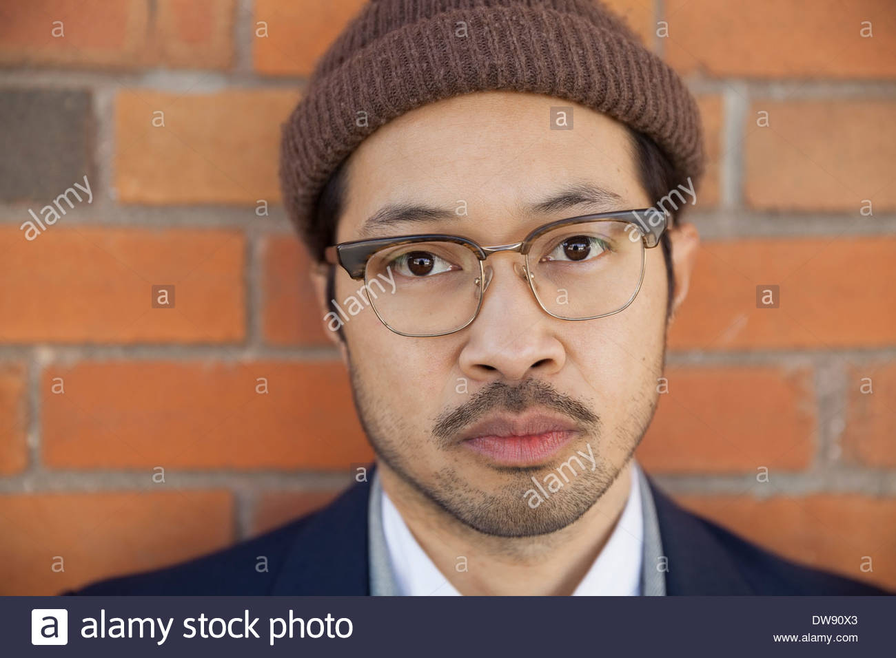 Close-up portrait of confident man against brick wall - Stock Image