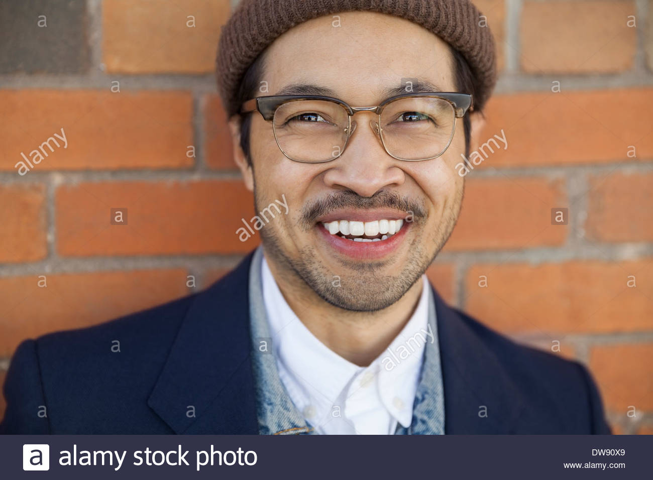 Close-up portrait of smiling man against brick wall - Stock Image