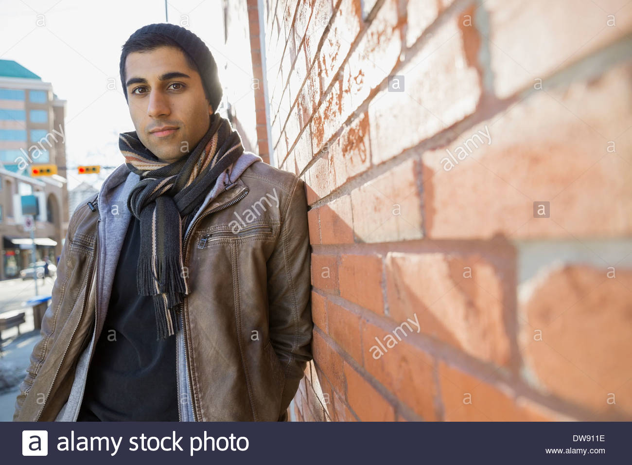 Portrait of confident man leaning against brick wall - Stock Image