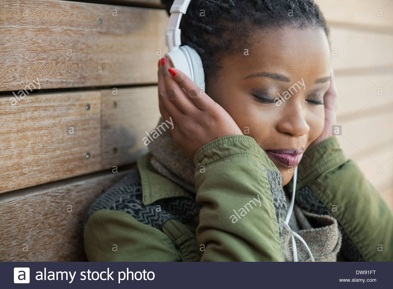 Relaxed woman listening to music outdoors - Stock Image
