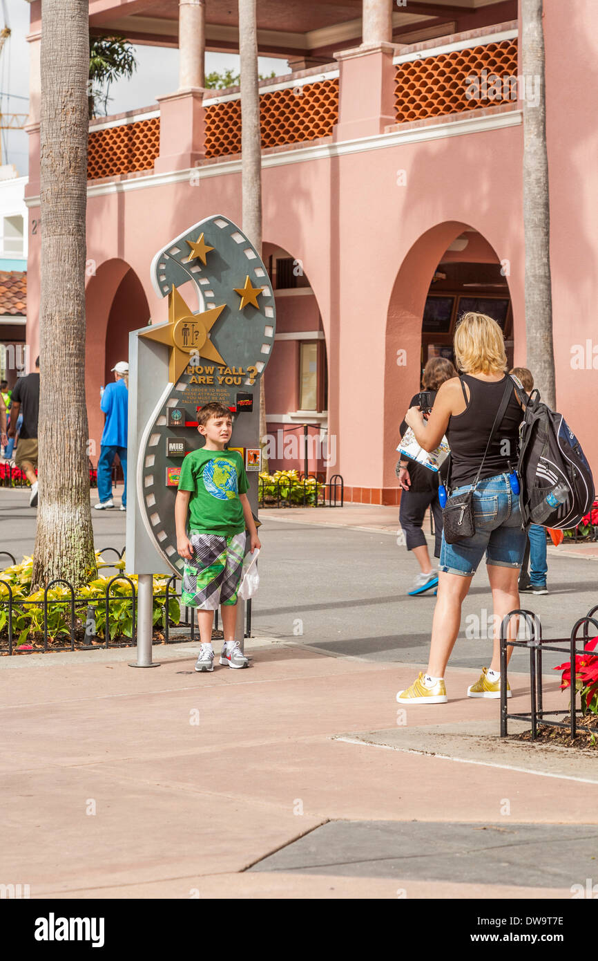 Mother takes photo of son at height chart near entrance at Universal Studios theme park in Orlando, Florida - Stock Image