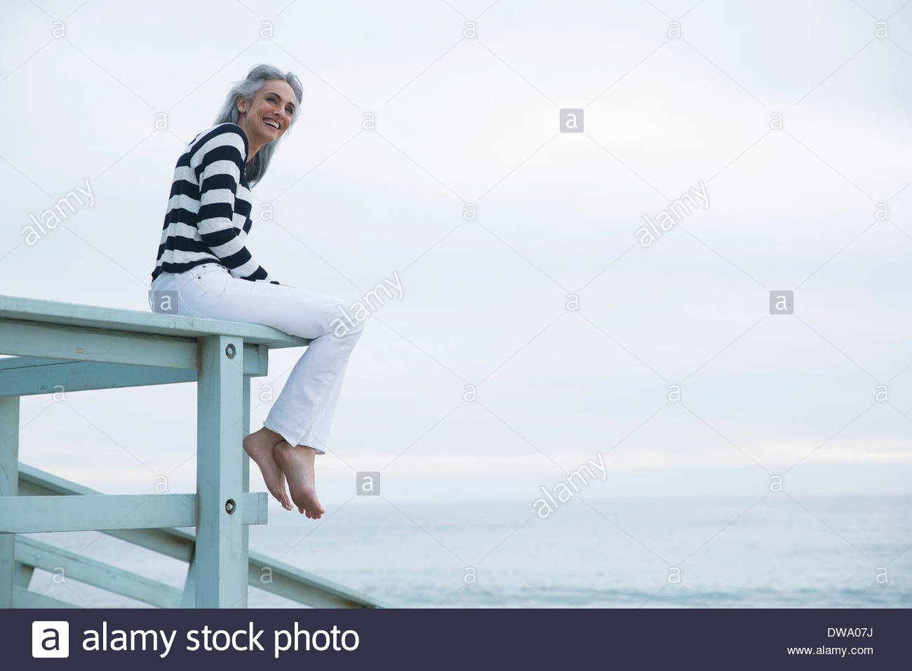 Mature woman sitting on beach house balcony, Los Angeles, California, USA - Stock Image