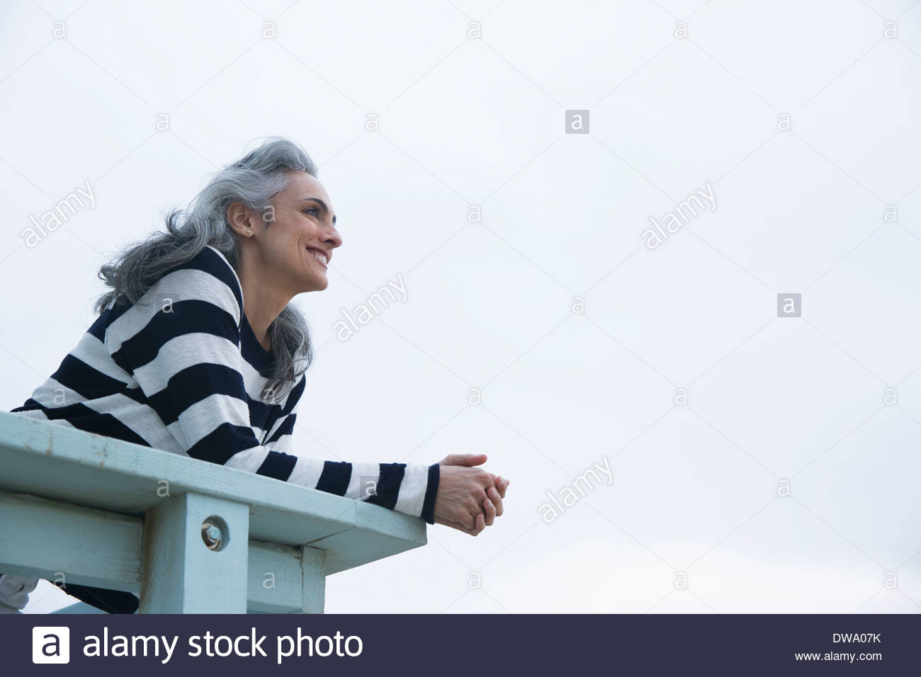 Mature woman watching from beach house balcony, Los Angeles, California, USA - Stock Image