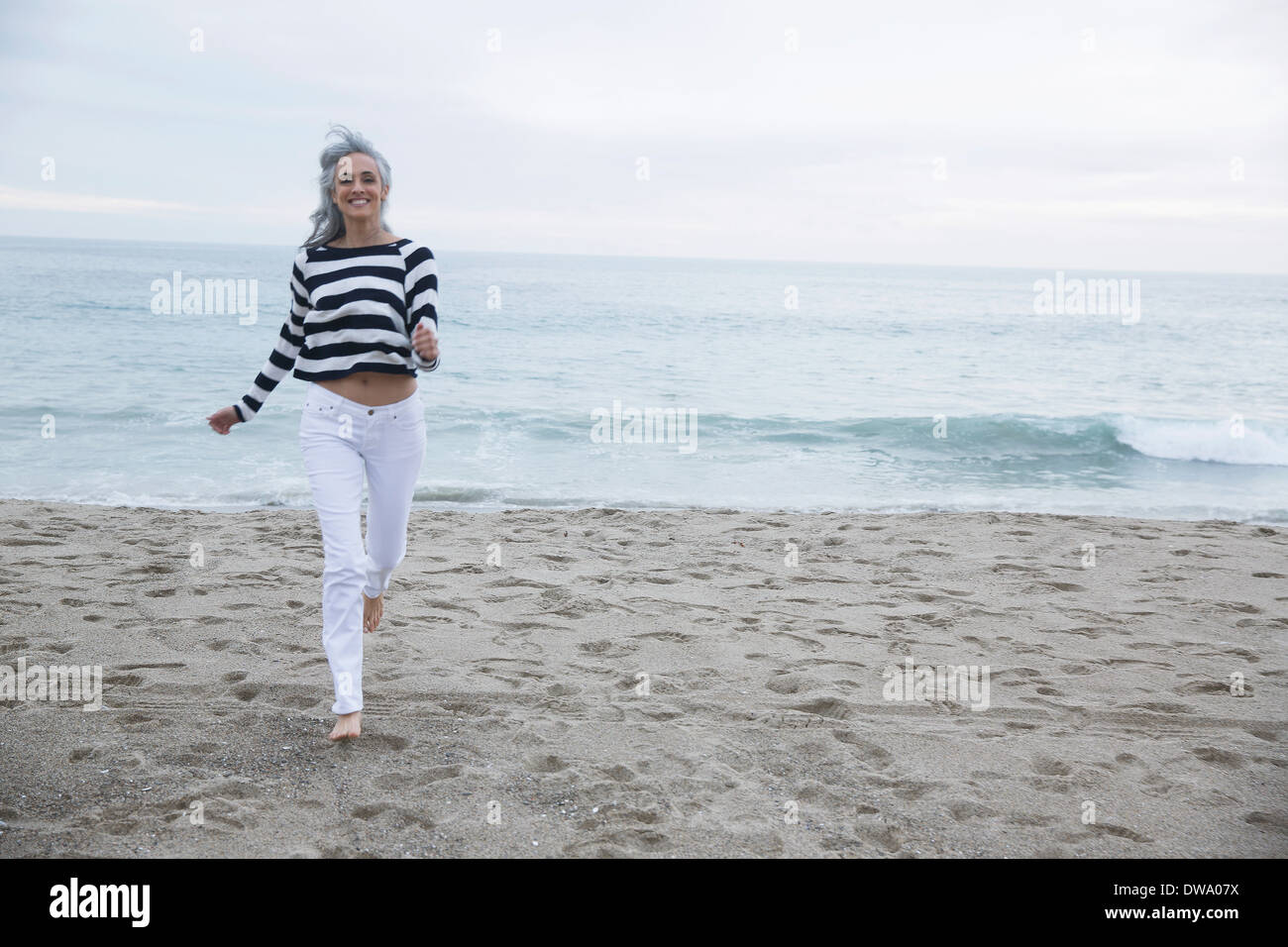 Mature woman running on beach, Los Angeles, California, USA - Stock Image