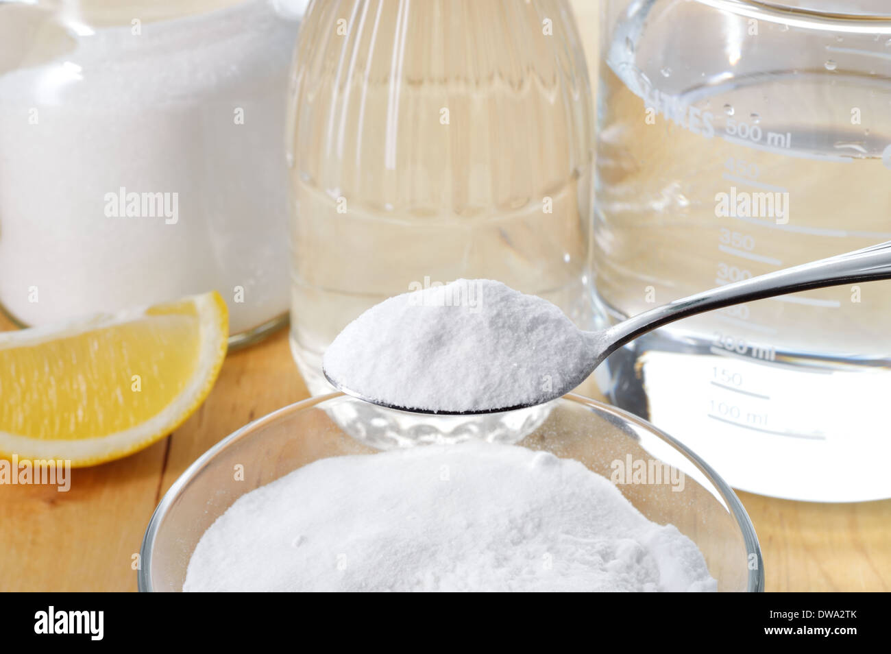 Eco-friendly natural cleaners. Vinegar, baking soda, salt, lemon and cloth on wooden table. Homemade green cleaning. - Stock Image