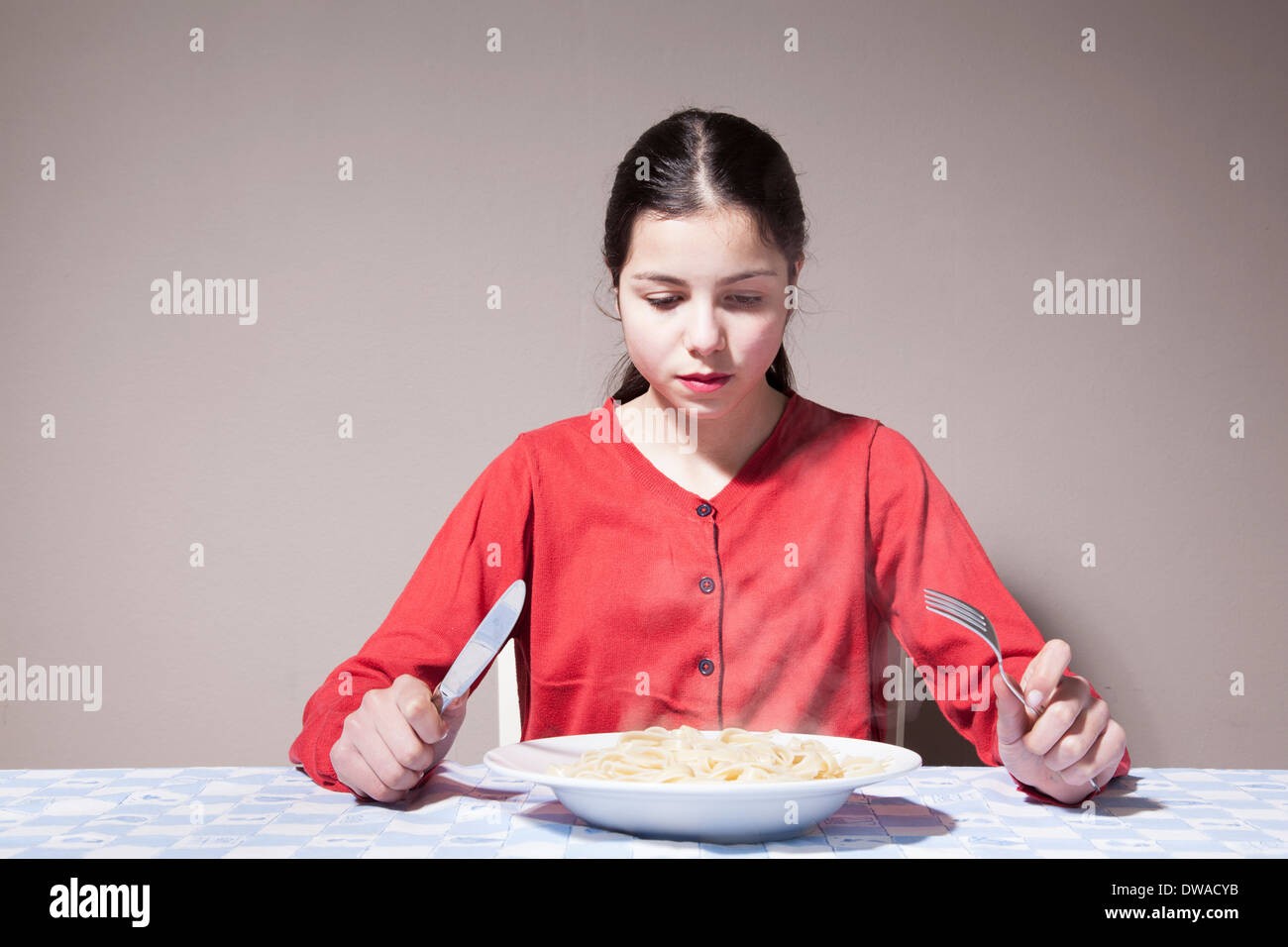 Teenage girl eating pasta - Stock Image