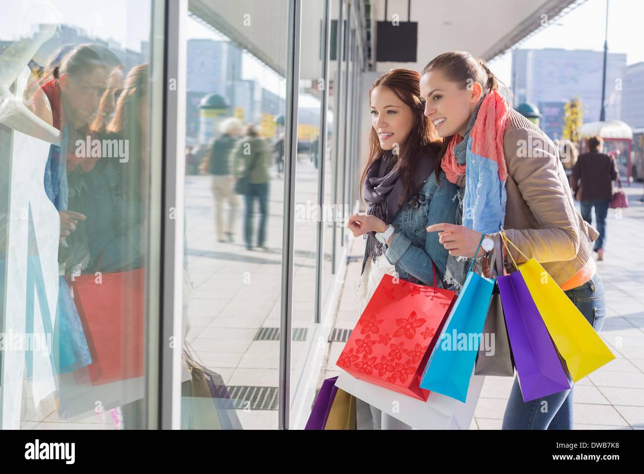 Shopaholic female friends window shopping - Stock Image