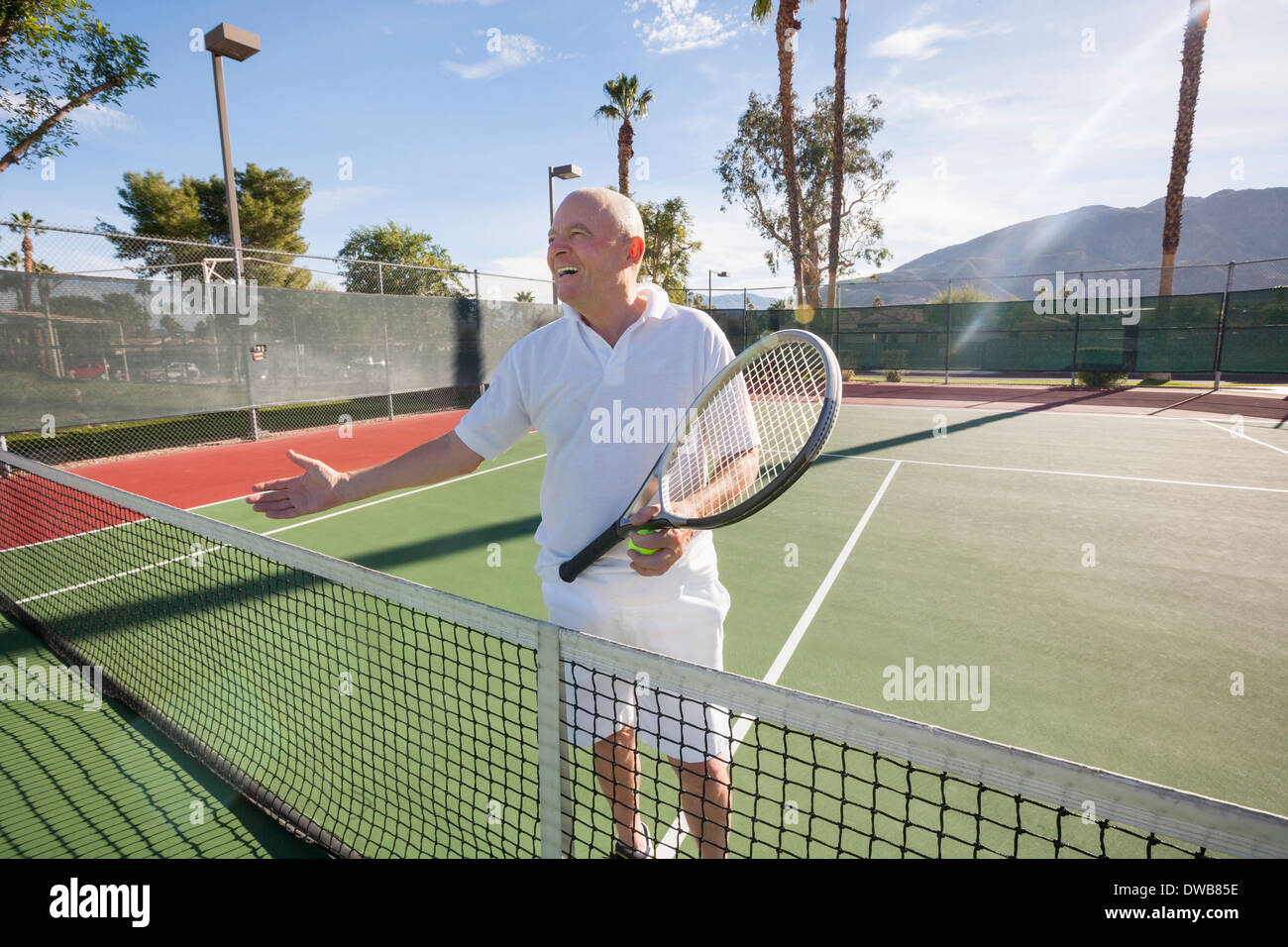 Happy senior male tennis player offering handshake on court - Stock Image