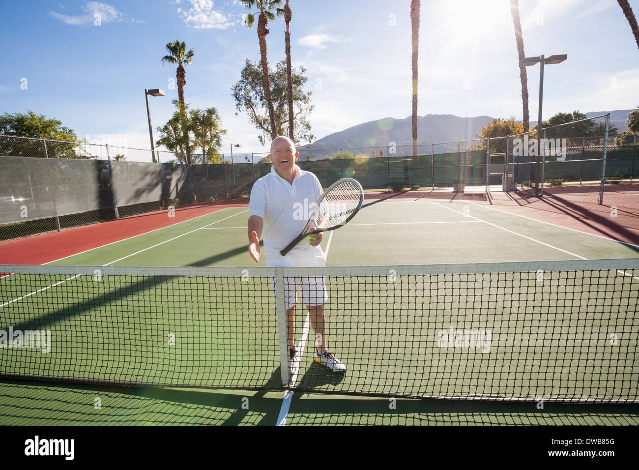 Portrait of senior tennis player offering handshake on court - Stock Image