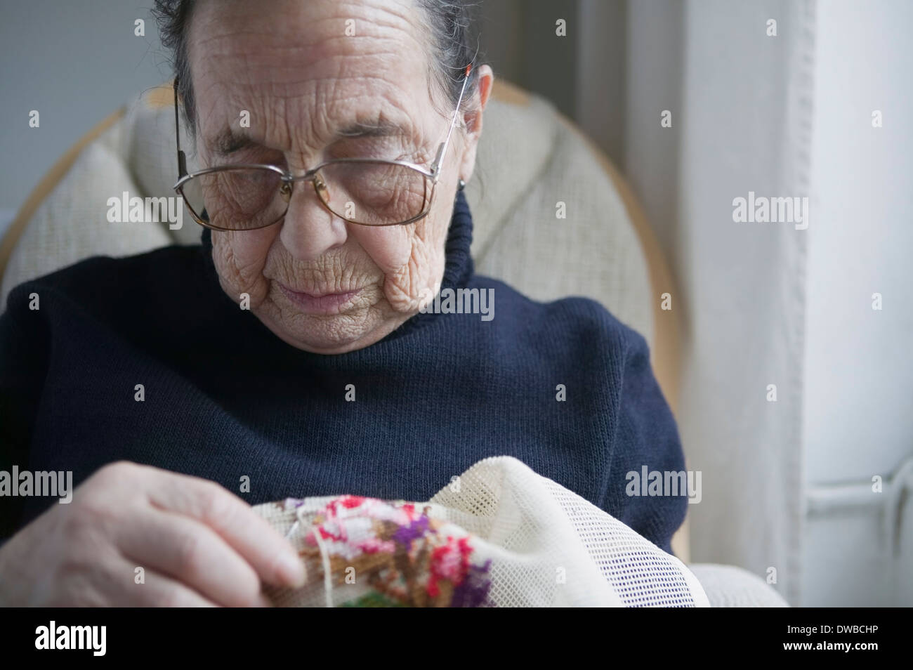 Senior woman doing cross stitch - Stock Image