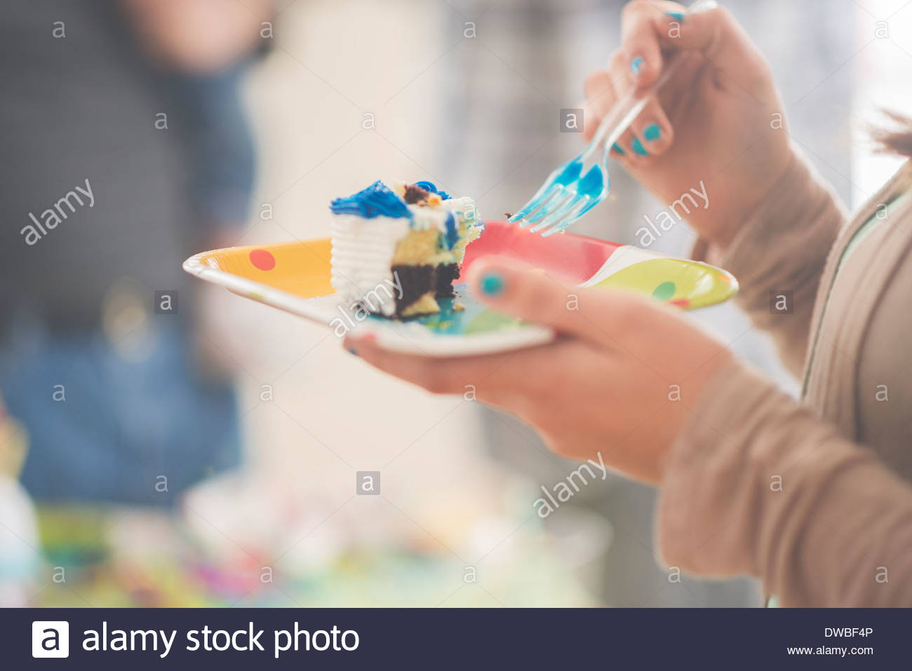 Close up of teenage girl eating slice of birthday cake - Stock Image