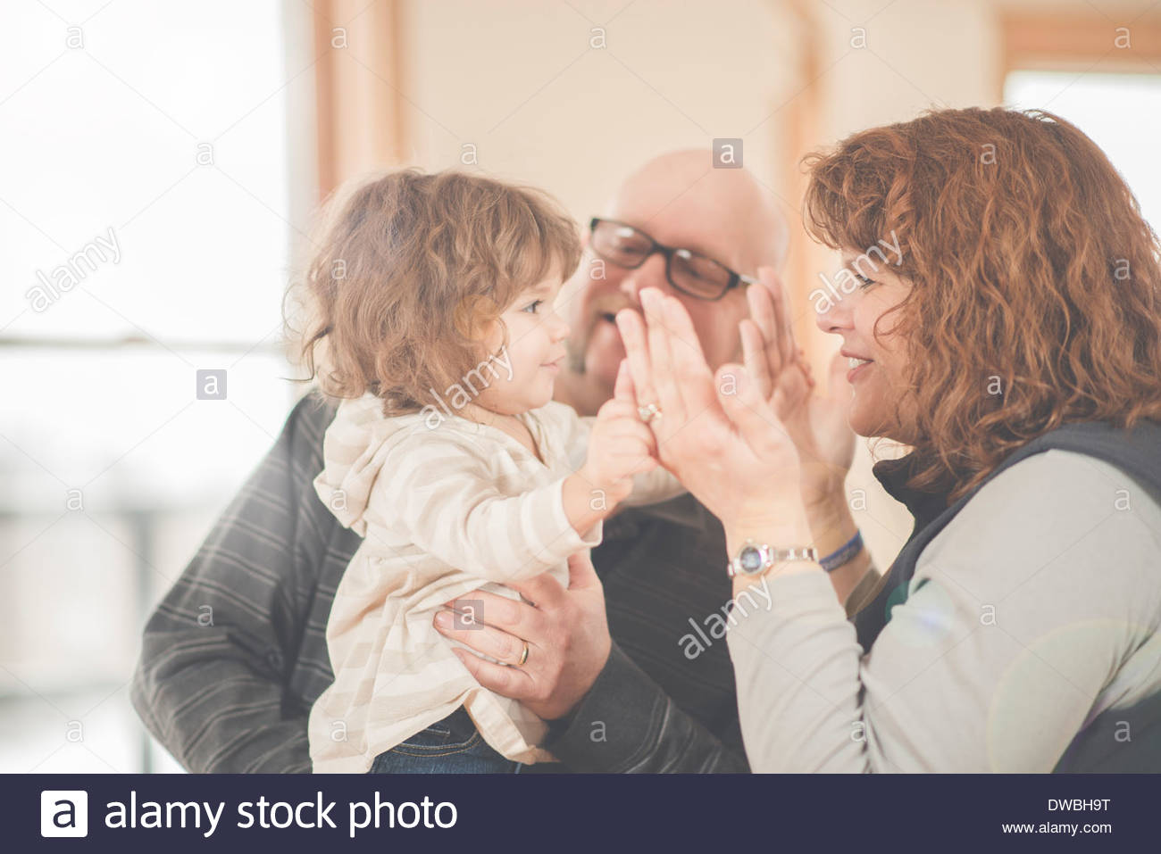 Female toddler and adoring grandparents - Stock Image