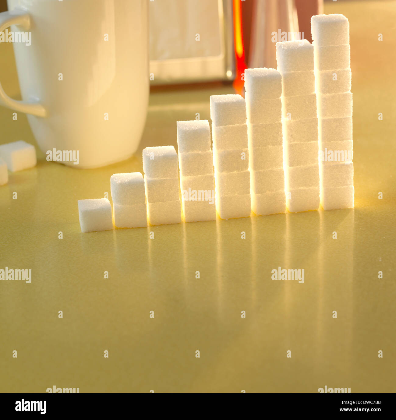 Stack of sugar cubes in the shape of a graph on a yellow table - Stock Image