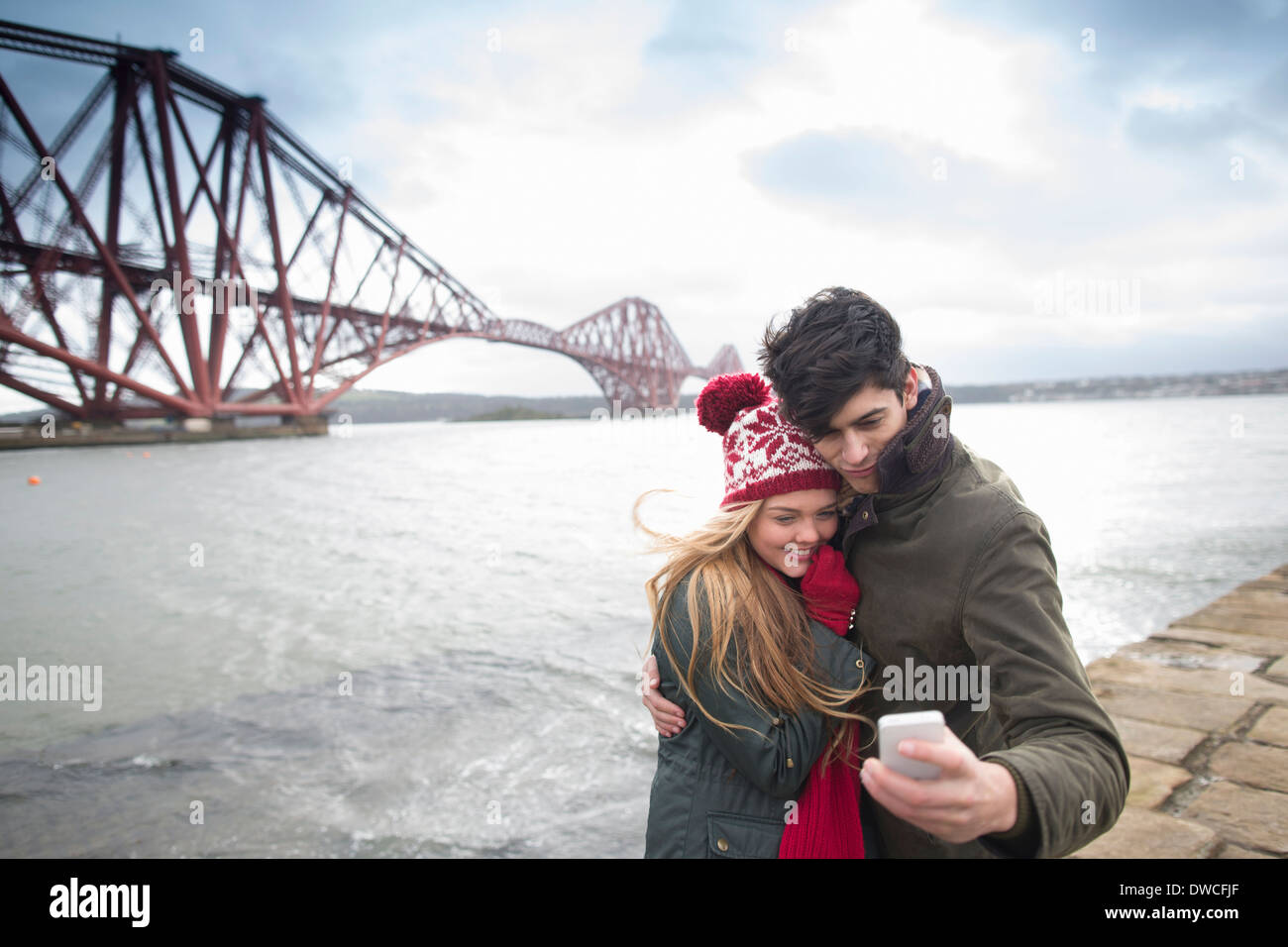 A young couple pose in front of the Forth Rail Bridge in Queensferry, near Edinburgh, Scotland - Stock Image