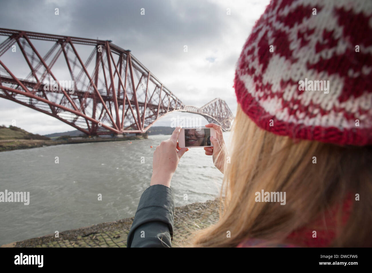 A young woman taking photograph of the Forth Rail Bridge in Queensferry, near Edinburgh, Scotland - Stock Image