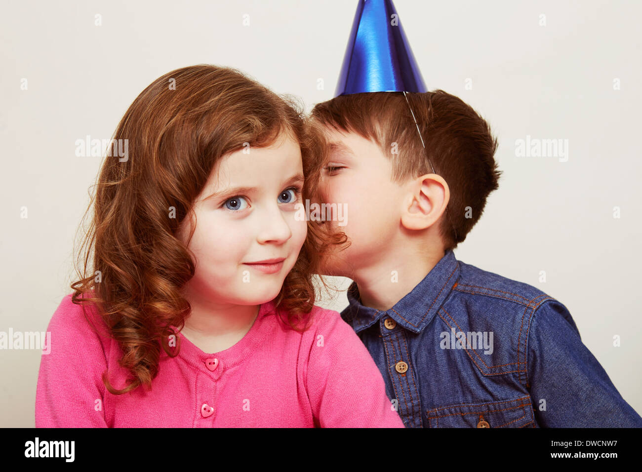 Boy wearing party hat whispering to girl Stock Photo