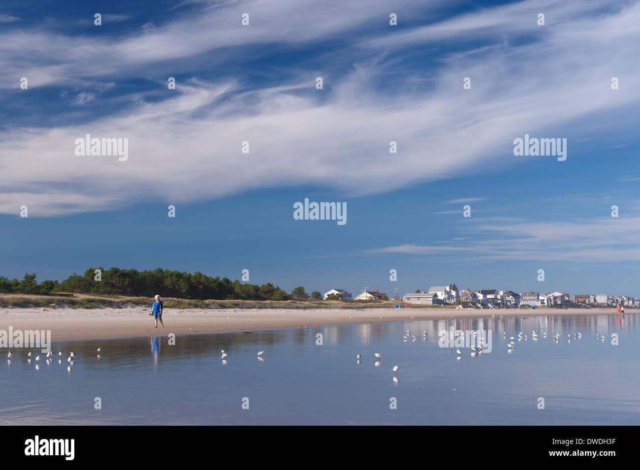 senior-woman-walking-on-the-beach-in-moody-maine-usa-DWDH3F.jpg
