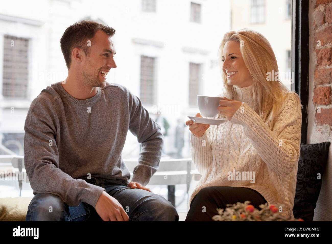Happy young couple spending leisure time at cafe - Stock Image