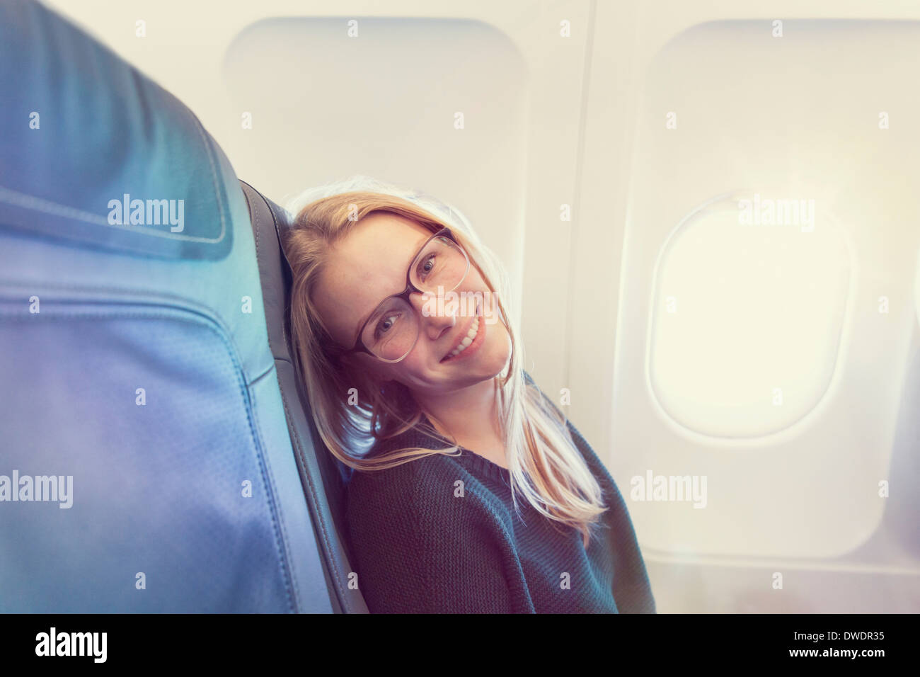 Smiling young woman in airplane, portrait - Stock Image