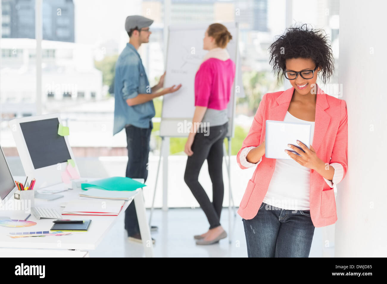 Artist using digital tablet with colleagues in at office - Stock Image