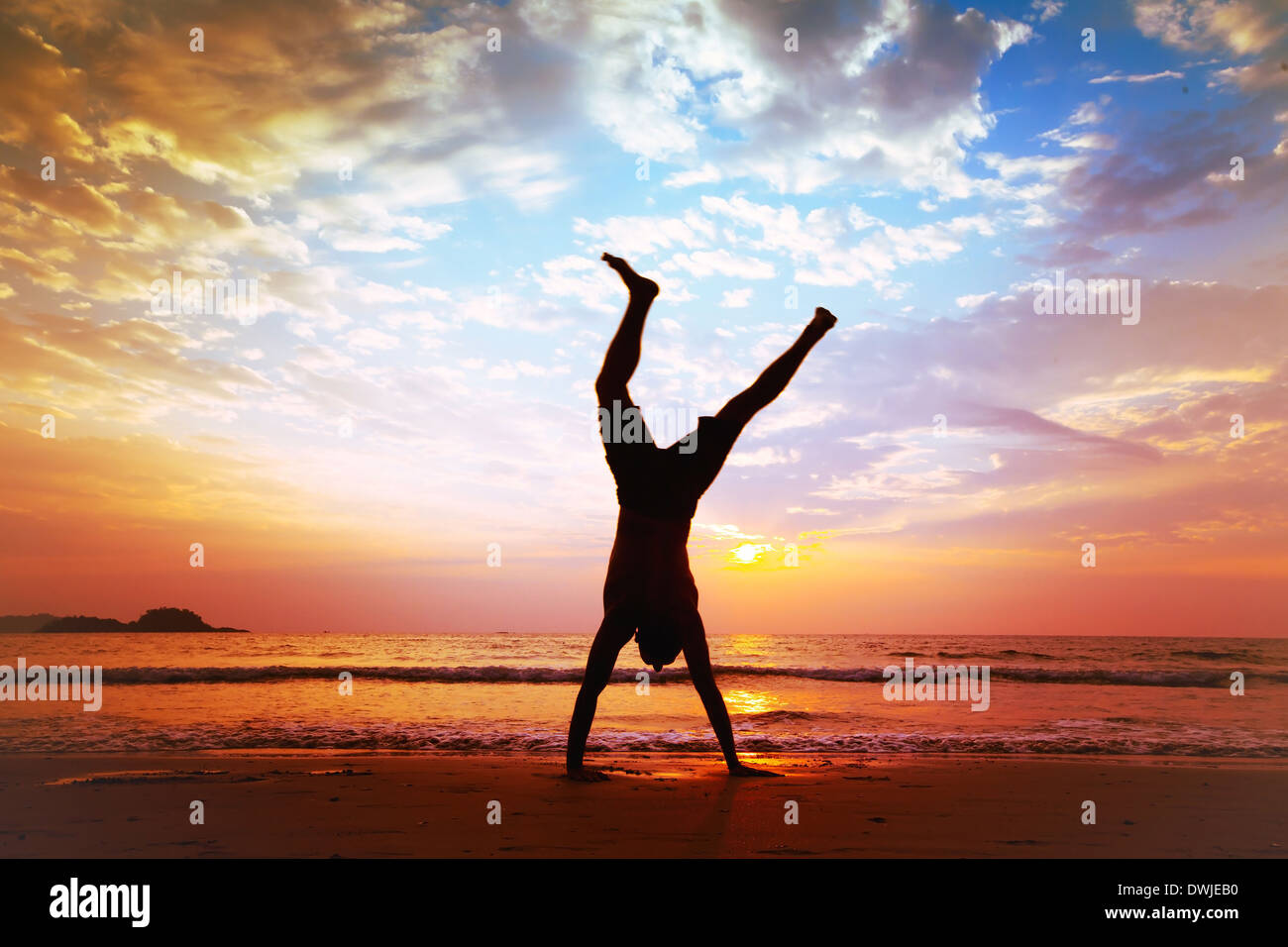 freedom and creativity, man jumping on the beach - Stock Image