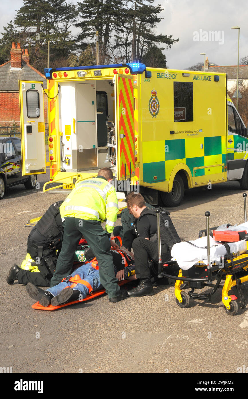 A road traffic accident casualty is tended to by ambulance crew and police officers - Stock Image