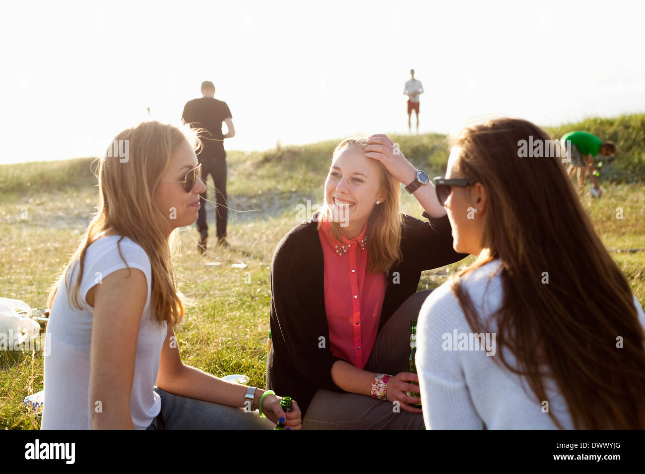 Happy female friends spending leisure time at beach - Stock Image