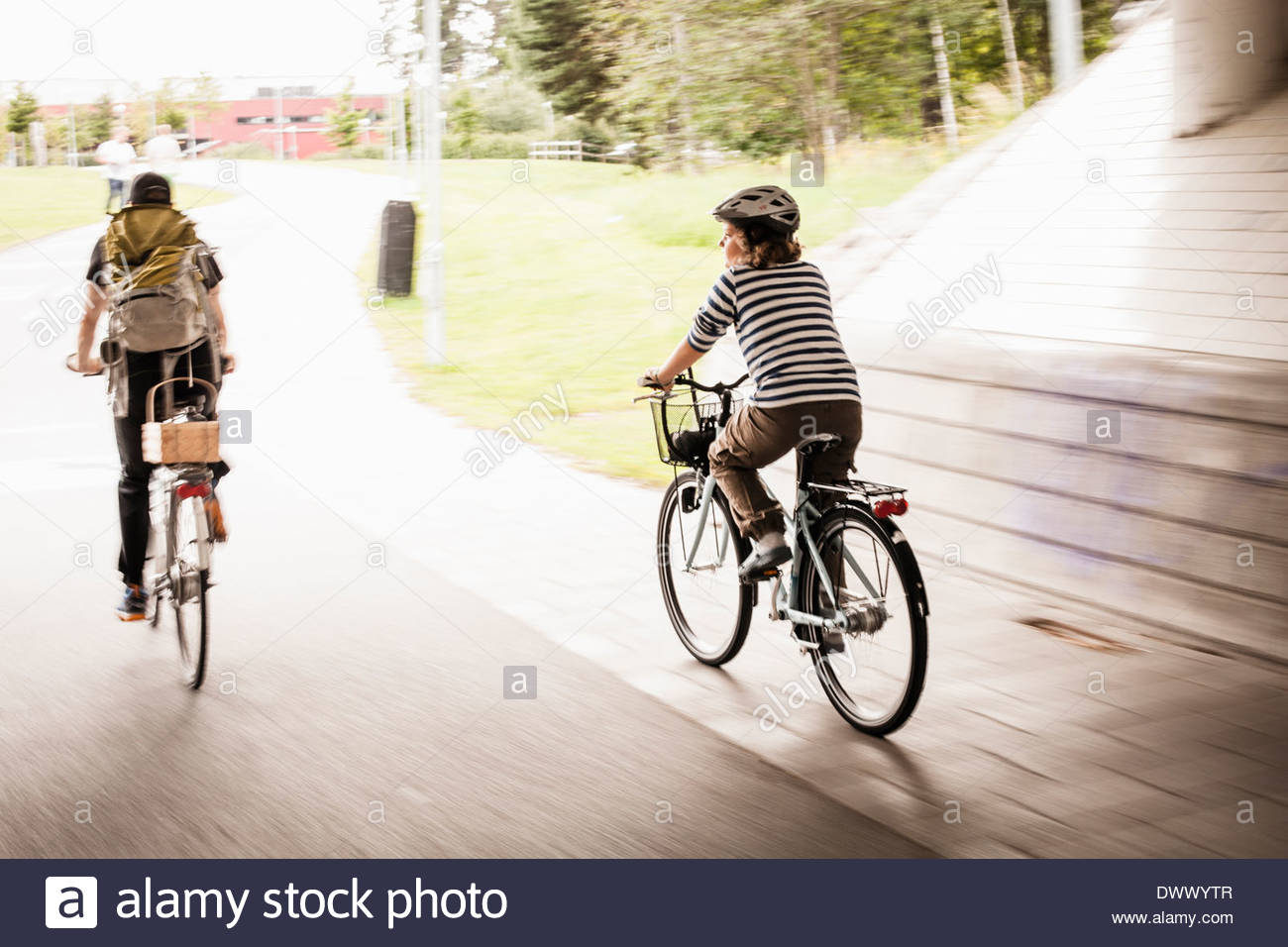 Blurred motion of father and daughter riding bicycles on street - Stock Image