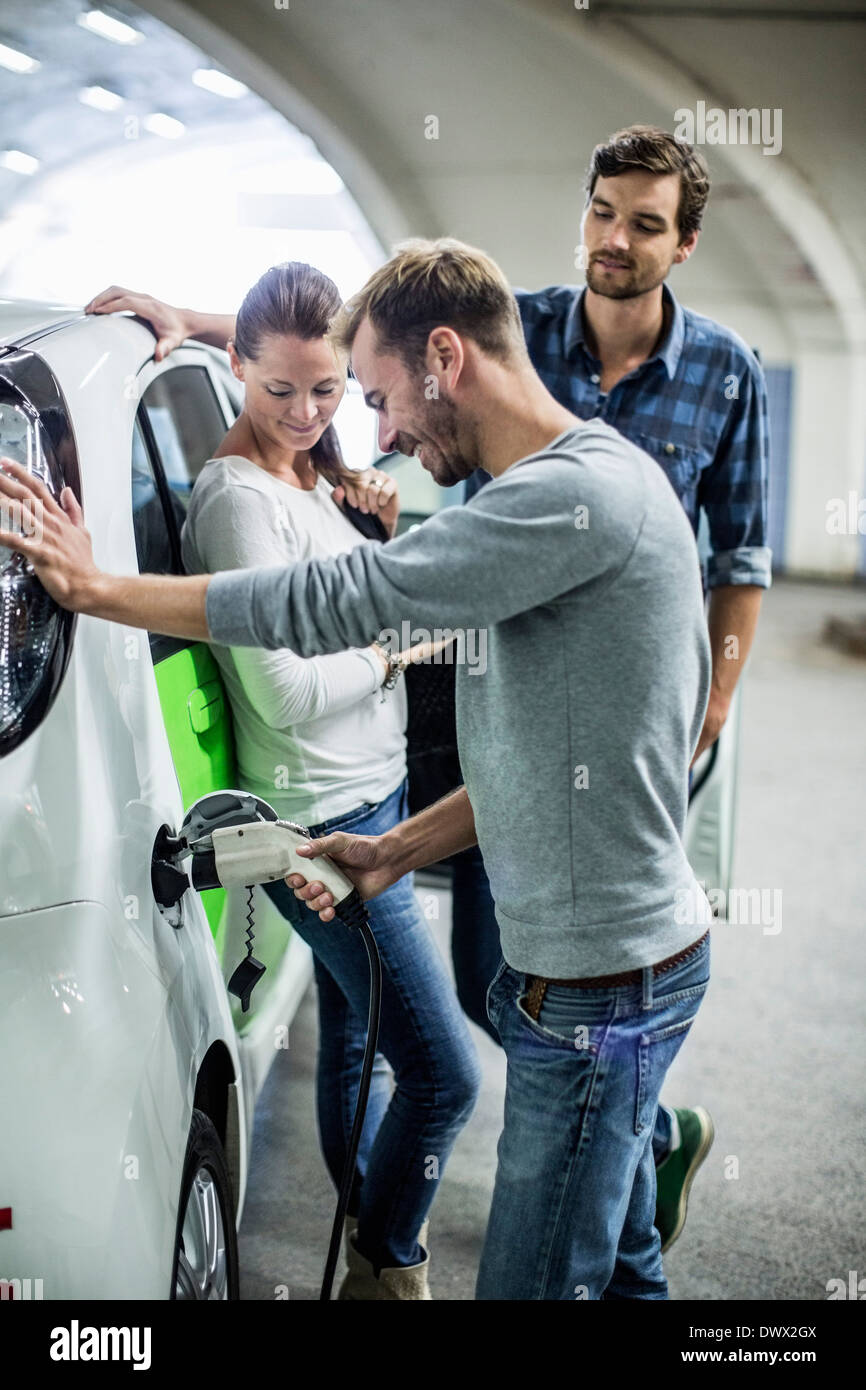 Friends looking at man charging electric car in gas station - Stock Image